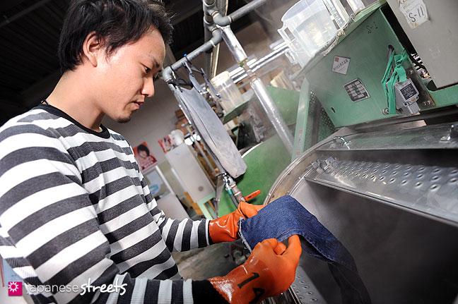 101104-6261 - An employee of Kouritsu, STUDIO D'ARTISAN's owner, tests a denim aging process